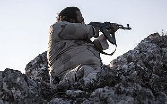 A Free Syrian Army fighter aims his weapon towards government forces during clashes in Telata village, a frontline located at the top of a mountain in the Idlib province, Syria, Sunday, Sept. 29, 2013 (photo credit: AP)