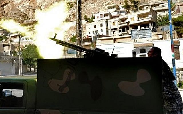 A Syrian army soldier fires a heavy machine gun during clashes with rebels in the village of Maaloula, northeast of Damascus, Syria, on Saturday, September 7, 2013. (photo credit: AP/SANA)