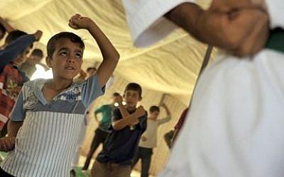 Syrian refugee children look at their Korean Taekwondo instructor at Zaatari refugee camp near Mafraq, Jordan, Tuesday, Sept. 17, 2013 (photo credit: AP/Bela Szandelszky)