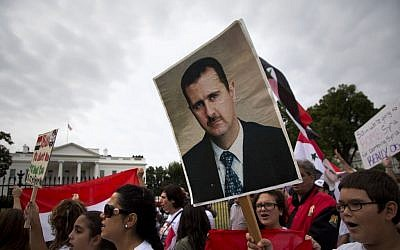 Protesters carry an image of Syrian President Bashar Hafez al-Assad during a demonstration against US military action in Syria, Monday, Sept. 9, 2013, in front of the White House in Washington (photo credit: AP/Carolyn Kaster)