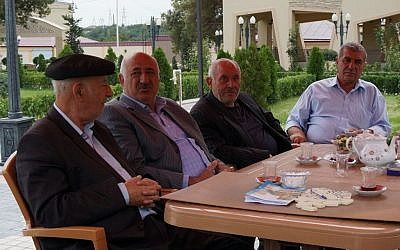 Yedidia Yehuda, right, sitting with Jewish lawmaker Yevda Abramov, second from left, in a Jewish tea house in Krasnaiya Sloboda, Aug. 22, 2013. (photo credit: Cnaan Liphshiz/JTA)