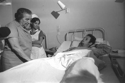 Meir visiting the wounded on the tenth day of the war (Photo credit: Chananiah Herman/ GPO)