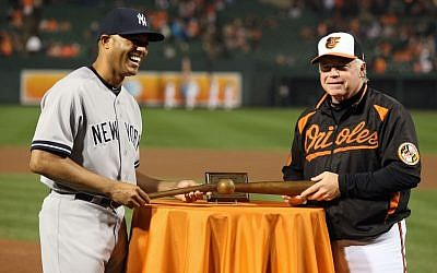 Baltimore Orioles manager Buck Showalter presenting Omri Amrany's sculpture of a broken bat as a retirement gift to New York Yankees pitcher Mariano Rivera, Sept. 12, 2013. (photo credit: Todd Olszewski/Courtesy of the Baltimore Orioles)