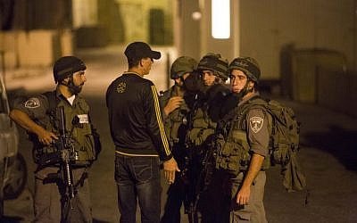 Israeli soldiers speak with a local resident near a shooting scene in the city of Hebron on September 22, 2013 (photo credit: Yonatan Sindel/Flash90)
