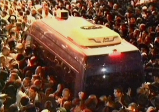 Mourners throng around a car carrying Rabbi Ovadia Yosef's body during the late rabbi's funeral in Jerusalem, Monday, October 7, 2013 (screen capture: YouTube)