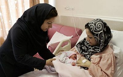 Iranian nurse Zahra Akbarzadeh, left, gives one-day-old baby girl Setayesh to her mother, Tayyebeh Sadat Bidaki, to feed her at the Mehr hospital, in Tehran, Sunday, July 29, 2012 (photo credit: AP/Vahid Salemi)