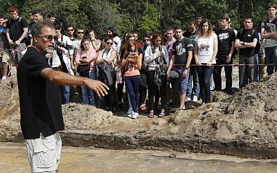 Israeli archaeologist Yoram Haimi talks to a group of young people from the Dror School in Israel about his findings at the site of the former German Nazi death camp Sobibor, in eastern Poland. (photo credit: AP Photo/Czarek Sokolowski, File)