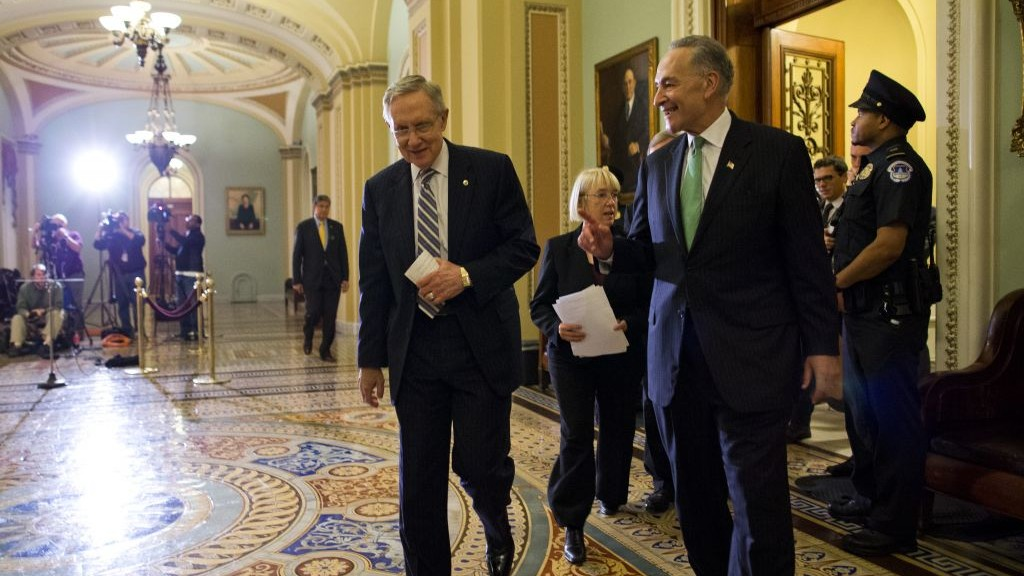Senate Majority Leader Sen. Harry Reid, left, walks off the Senate floor with Sen. Chuck Schumer after voting to avoid a financial default and reopen the government after a 16-day partial shutdown, in October 2013 (photo credit: AP/Evan Vucci)