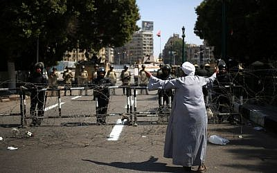 An Egyptian man gestures to Egyptian Army soldiers standing guard at an entrance to Tahrir Square, in Cairo, Egypt, on Sunday, October 6, 2013. (photo credit: AP/Khalil Hamra)