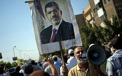 Supporters of Egypt's ousted president Mohammed Morsi (seen on a poster) chant slogans against Egyptian Defense Minister Gen. Abdel-Fattah el-Sissi, during a protest in Cairo (photo credit: AP/Khalil Hamra)