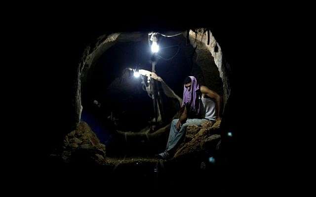 A Palestinian sits in one of Gaza's smuggling tunnels (photo credit: Hatem Moussa/AP)