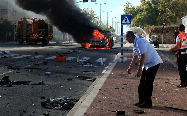 Israeli rescue forces extinguish the fire after a car exploded in Ashkelon on October 24, 2013. Two men were seriously injured in the blast, and one later died of his wounds while hospitalized. The attack is beleived to be criminally motivated. (Photo credit: Edi Israel/Flash90)
