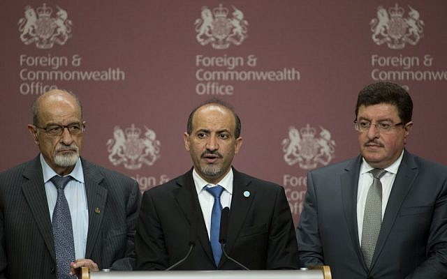 Members of the Syrian Opposition Coalition, including the group's President Ahmed Jarba, center, Heitham Al-Maleh, left, and Salem Al-Muslit speak to the media at the British Foreign Office in London Tuesday, Oct. 22, 2013 (photo credit: AP/Alastair Grant)