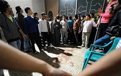Egyptians gather at a Coptic Christian church in the Waraa neighborhood of Cairo late Sunday, Oct. 20, 2013 after gunmen on motorcycles opened fire, killing a woman and wounding several people.  (AP Photo/Mohsen Nabil)