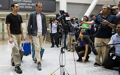 John Greyson, right, and Tarek Loubani arrive at the Pearson International Airport in Toronto, Friday Oct. 11, 2013. Two Canadians who spent seven weeks in an Egyptian prison without being charged have returned home to Canada. (AP Photo/The Canadian Press, Mark Blinch)