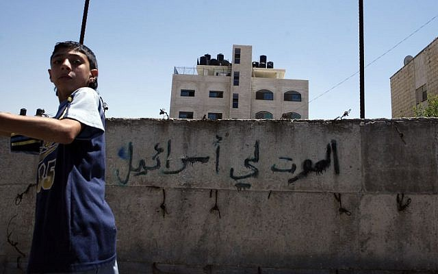 A Palestinian boy walks past a wall painted with graffiti reading 'Death to Israel' in the northern Jerusalem Palestinian neighborhood of Beit Hanina, July 2008 (Michal Fattal/Flash90)