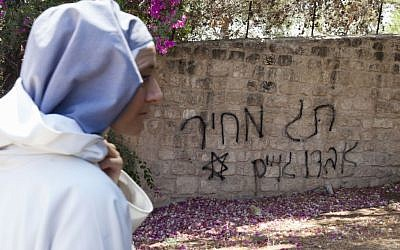 Illustrative photo of a nun walking by price tag graffiti at a church near Beit Shemesh in August. (photo credit: Flash90)