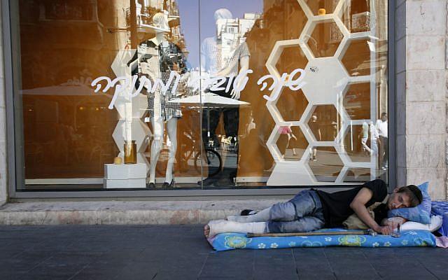 A homeless man sleeps on the edge of the road on Jaffa Street in Jerusalem. Sep 16 2013. (photo credit: Sliman Khader/FLASH90)