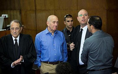 Former prime minister Ehud Olmert, seen with his lawyers in court as he prepares to give testimony at the Holyland trial, on October 1, 2013. (photo credit: Tal Shahar/Pool/Flash90)