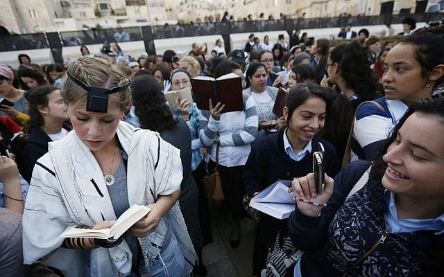 Young ultra-Orthodox women ridicule a prayer shawl-clad female worshiper at the Western Wall during a monthly prayer session of the Women of the Wall group, Friday, October 4, 2013 (photo credit: Miriam Alster/Flash90)