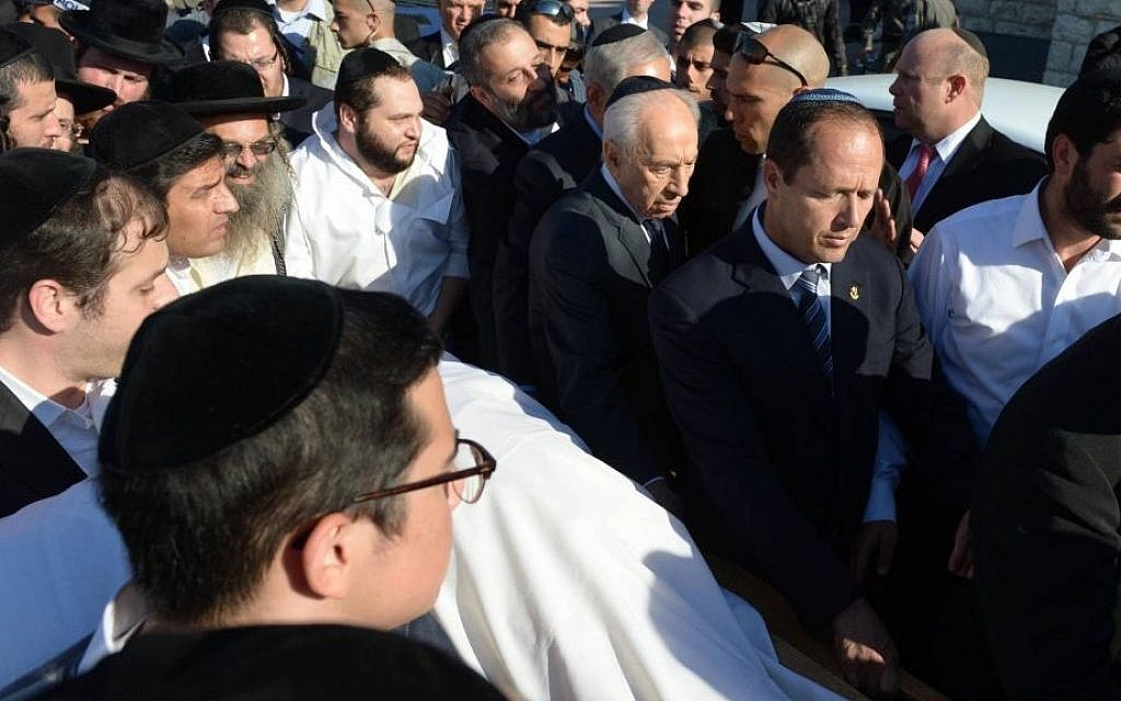 President Shimon Peres, Prime Minister Benjamin Netanyahu, Shas party leader Aryeh Deri and Jerusalem Mayor Nir Barkat are seen helping carry the body of Shas spiritual leader Rabbi Ovadia Yosef, who passed away earlier at the age of 93, in Jerusalem, on October 7, 2013. (photo credit: Mark Neyman/GPO/Flash90)