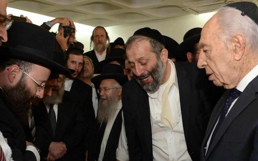 Shas party leader Aryeh Deri (center) cries as he stands with Israeli President Shimon Peres (right) near the body of Shas spiritual leader Rabbi Ovadia Yosef,  in Jerusalem on October 7, 2013. (photo by Mark Neyman/GPO/Flash90