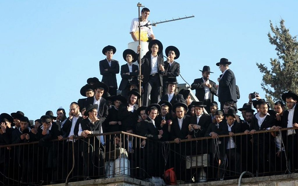 Mourners on a rooftop near the Porat Yosef yeshiva in Jerusalem, where hundreds of thousands are gathering for the funeral of Rabbi Ovadia Yosef, in Jerusalem, on October 7, 2013. (photo credit: Nati Shohat/Flash90)