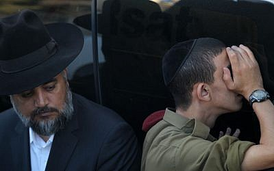 A soldier and an ultra-Orthodox man at the funeral of Rabbi Ovadia Yosef in Jerusalem, October 7, 2013 (photo credit: Nati Shohat/Flash90)