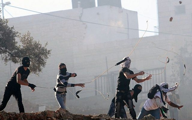 Palestinians throw rocks near Ramallah on October 12, 2013 (Illustrative photo: Issam Rimawi/Flash90)
