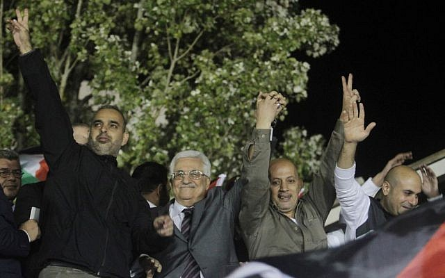 Palestinian President Mahmoud Abbas, second from left, waves with released Palestinian prisoners coming from Israeli jails during celebrations at Abbas' headquarter in the West Bank town of Ramallah, October 30, 2013. (photo credit: Issam Rimawi/Flash90)