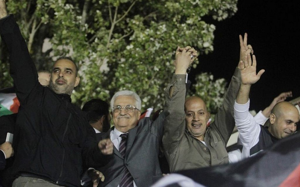 Palestinian Authority President Mahmoud Abbas, second left, flanked by newly released Palestinian prisoners, greets the crowd in Ramallah, on October 30, 2013 (Issam Rimawi/Flash90)