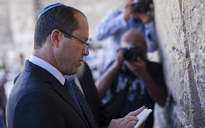 Jerusalem Mayor and candidate for the municipal elections, Nir Barkat prays at the Western Wall in Jerusalem old city on October 22, 2013 during Israel's municipal elections. Israelis are voting in municipal elections in a poll likely to be shunned by much of the public who see local authorities as tainted by corruption. (photo credit: Yonatan Sindel/Flash90)