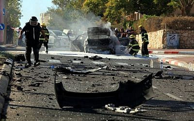 A bomb squad investigates the charred remains of a car after a powerful explosion in the coastal city of Ashkelon on Thursday afternoon. Two men were seriously injured in the blast, and one later died of his wounds while hospitalized. (photo credit: Edi Israel/Flash90)