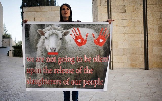 A woman holds a sign against the release Tuesday October 29, 2013 of Palestinian prisoners outside of the High Court in Jerusalem. (Photo credit: Flash90)
