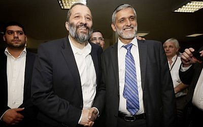 Shas party leader MK Aryeh Deri (left) seen shaking hands with fellow Shas MK Eli Yishai, after a meeting in the Knesset aimed to heal their feud, October 30, 2013. (Photo credit: Miriam Alster/FLASH90)