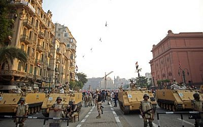 Egyptian military helicopters fly overhead as soldiers stand guard at an entrance to Tahrir Square, in Cairo, Egypt, Oct. 6, 2013 (photo credit: AP/Khalil Hamra/File)