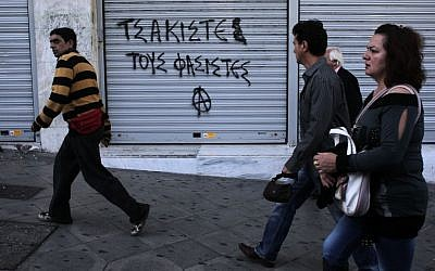 Pedestrians walk past graffiti that reads 'crush the fascists' in Athens' Syntagma square on Friday Oct. 11, 2013. Anti-fascist messages in public spaces around Athens increased after lawmakers and members of the extreme right party Golden Dawn were jailed. (photo credit: AP Photo/Dimitri Messinis)