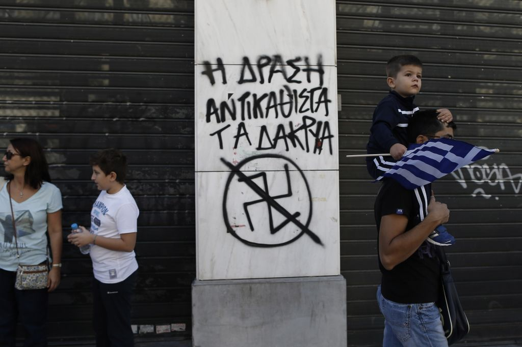 A child holds a Greek flag as he passes with his father next to graffiti depicting an anti Nazi Symbol and reading in Greek 'Action replace tears' during a parade commemorating Greece's entry in World War II in 1940, in central Athens, on Monday, Oct. 28, 2013. (photo credit: AP Photo / Petros Giannakouris)
