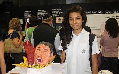 A student with her art at the 'Oasis of Survival and Hope' exhibit in Hong Kong. (photo credit: Erica Lyons)