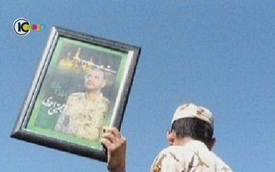 A mourner holds a photo of the late Iranian cyber war operative Mojtaba Ahmadi. Reports that he was assassinated were denied by the Iranian Revolutionary Guard who said he died in a 'horrific incident.' (Screenshot/Channel 10)