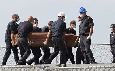The casket of one of the migrants who died when their boat capsized off in the Canal of Sicily is carried aboard a Italian Navy ship at the Lampedusa island harbor, Saturday, Oct. 12, 2013 (photo credit: AP/Amedeo Fragapane)