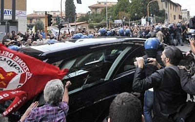 A woman holding a flag of Italian Communist Refoundation Party thumps her fist on the hearse carrying the coffin of Nazi war criminal Erich Priebke as it arrives at the Society of St. Pius X, a schismatic Catholic group, in Albano Laziale, on the outskirts of Rome, Tuesday, Oct. 15, 2013. (photo credit: AP Photo/Lapresse)