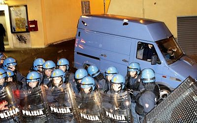 A van allegedly carrying the coffin of Nazi war criminal Erich Priebke is protected by policemen in riot gear as it leaves the Society of St. Pius X headquarters, a schismatic Catholic group, where his funeral was scheduled to take place in Albano Laziale, on the outskirts of Rome on Tuesday, October 15, 2013. (photo credit: AP/Riccardo De Luca)