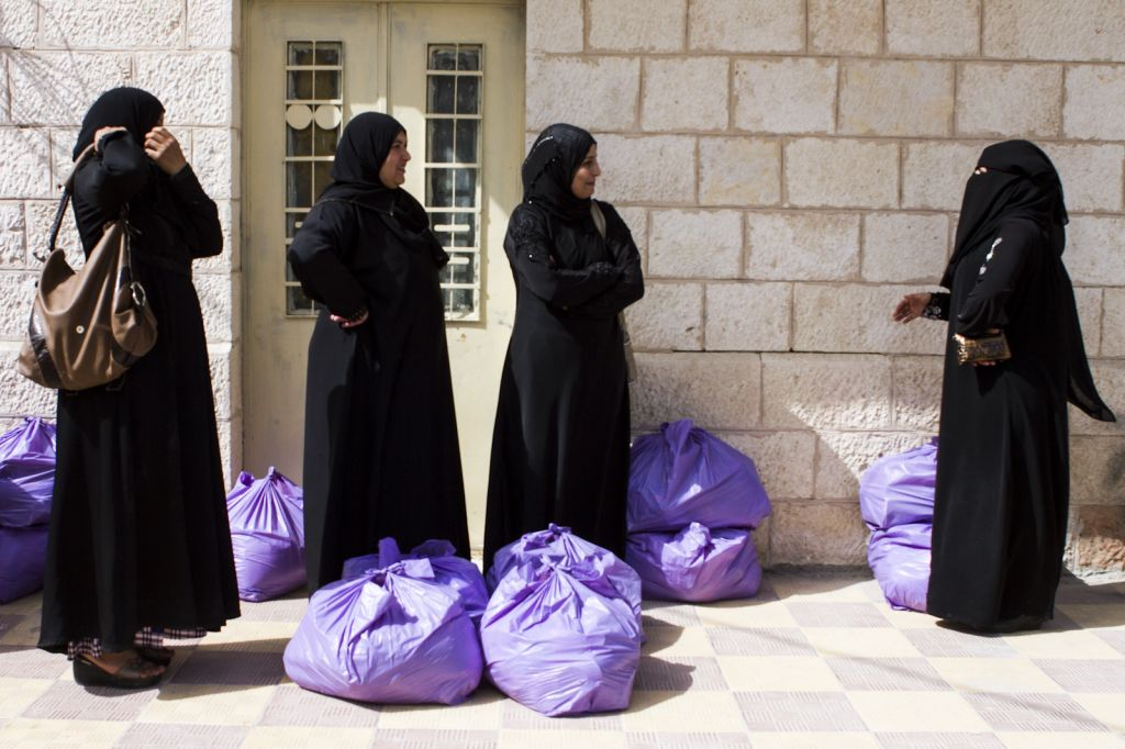 Syrian women outside the NGO's office after receiving their distribution bags (photo credit: Mickey Alon)
