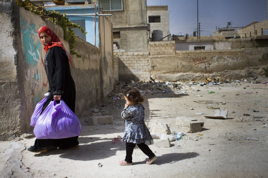 A Syrian woman carries her goods as her young daughter trails behind. (photo credit: Mickey Alon)
