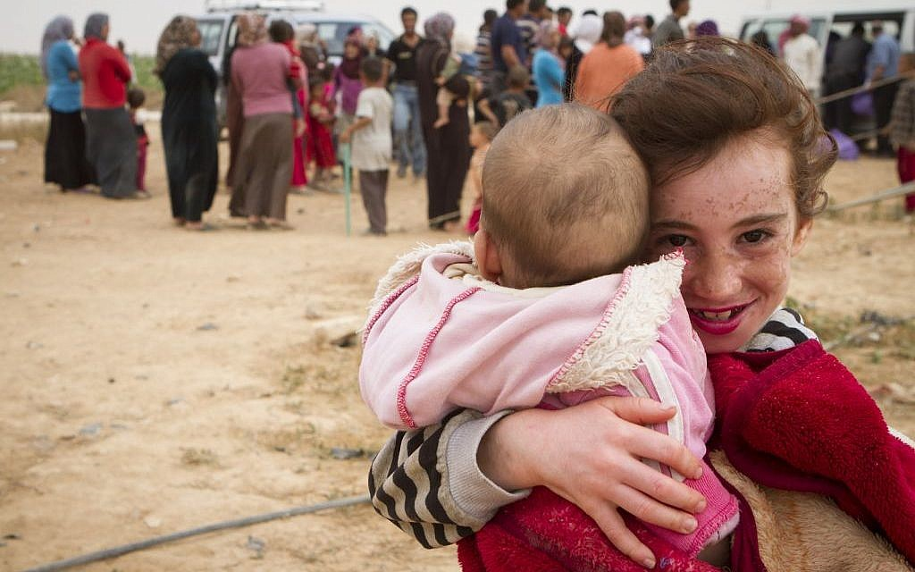 A Syrian refugee child holds her little sister as her family queues for aid behind her. (photo credit: Mickey Alon)