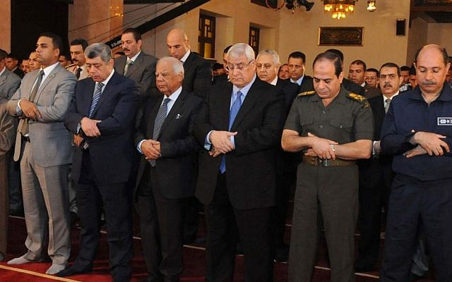 Interim Egyptian President Adly Mansour, center, interim Prime Minister Hazem el-Beblawi, fourth from left, and Defense Minister Gen. Abdel-Fattah el-Sissi, second from right, pray on the first day of Eid al-Adha, or Feast of Sacrifice, in Cairo, Egypt, in October. (photo credit: AP/Egyptian Presidency)