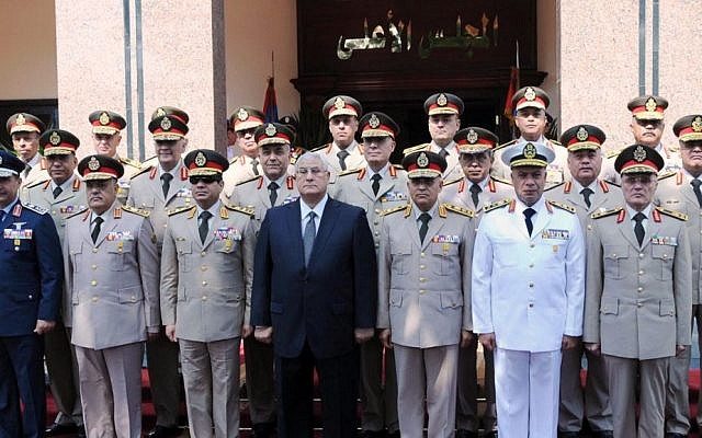 Egypt's interim President Adly Mansour, center, Defense Minister Abdel-Fatah el-Sissi, front row, third left, and other officials pose for a photograph during a visit to the Secretariat of the Armed Forces, part of celebrations marking the 40th anniversary of the start of the 1973 (Yom Kippur) war in which Egyptian forces made initial gains against Israel, Saturday, Oct. 5, 2013 (photo credit: AP)
