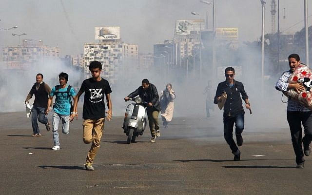 Egyptians run from tear gas after clashes erupted between Al-Azhar students and police forces during a protest in the Nasr City district of Cairo, Sunday, Oct. 20, 2013. (Photo credit: AP/Heba el-Kholy, El Shorouk Newspaper)