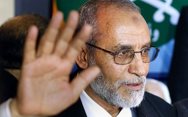 In this Saturday, Jan. 16, 2010 file photo, newly elected leader of Egypt's Muslim Brotherhood Mohammed Badie stands in front of the group's logo during his first press conference in Cairo, Egypt. Badie is one of the 35 defendants standing trial.